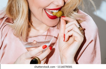 Cropped smiling woman holding glass of martini and eating olives.