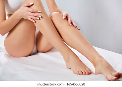 cropped smoothy legs of slim female, woman after laser epilation in beauty salon. skin and body care, hairless, hygiene concept