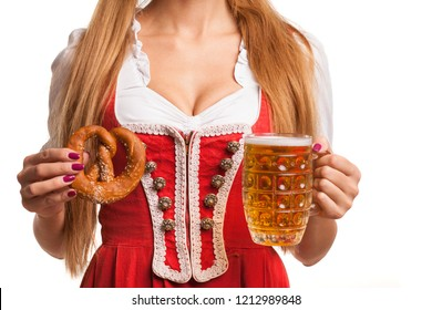 Cropped studio close up of a sexy big breasted bavarian girl in dirndl dress holding mug of beer and pretzel isolated on white. Oktoberfest waitress serving drinks. Sensuality, seduction, concept