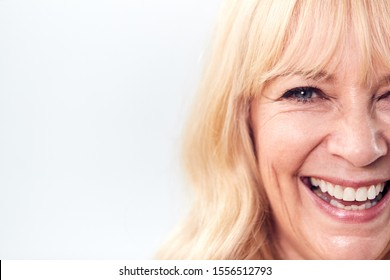 Cropped Studio Shot Of Laughing Mature Woman Against White Background At Camera