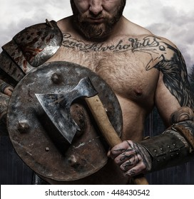 Cropped tattooed male's body with vikings shield and axe.