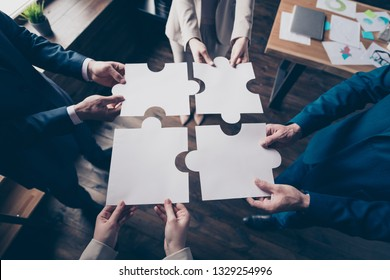 Cropped top above high angle view of stylish elegant sharks holding in hands fitting big large puzzle pieces together team building in loft industrial interior work place station