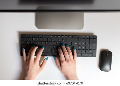 Cropped top view image of female hands typing on keyboard at office table.