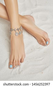 Cropped top view shot of woman's crossed legs isolated against the sandy background. The lady with light blue pedicure is wearing a silver anklet with coins. Fashionable women's summer accessory.