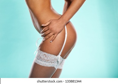 Cropped torso portrait of a woman with a sexy bottom posing in stockings and a suspender sideways to the camera against a blue background