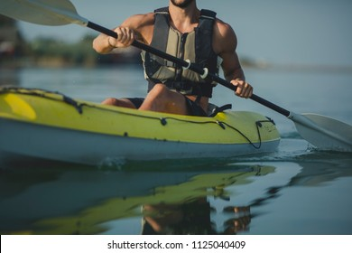 Cropped unrecognisable Caucasian man kayaker paddling on the river.