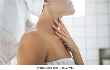 Cropped unrecognisable woman standing in bathroom and touching her skin.
