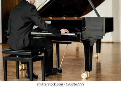 cropped unrecognizable male in suit playing piano on a stage. handsome guy gracefully play piano, practice before performance
