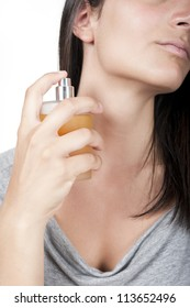 Cropped vertical image of a cute young woman with a perfume bottle in her hand.