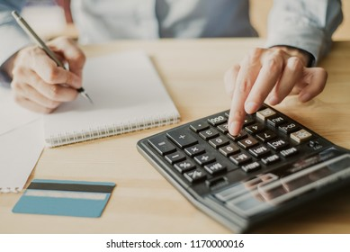 Cropped view of accountant counting on calculator, making notes and working and credit card