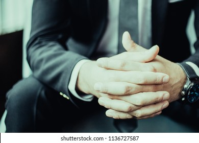 Cropped view of adult business man sitting with his hands clasped