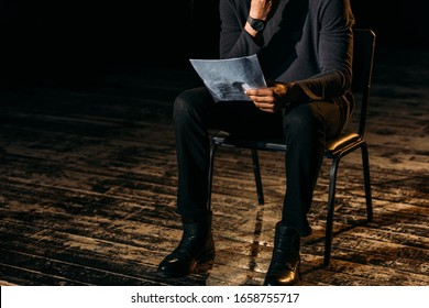 cropped view of african american actor holding scenario on stage during rehearse