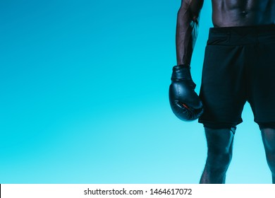 cropped view of african american boxer in shorts on blue background