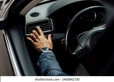 cropped view of african american businessman in suit touching air conditioning near steering wheel in car