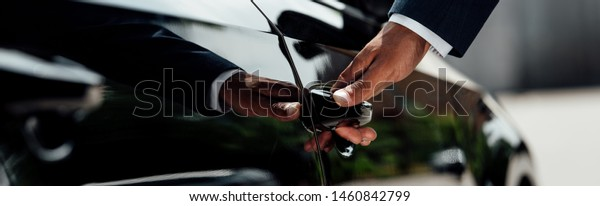cropped view of african american businessman in suit opening car door at sunny day, panoramic shot