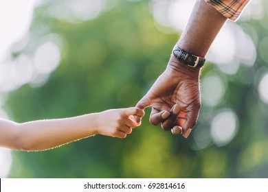 cropped view of african american grandfather holding hands with little granddaughter