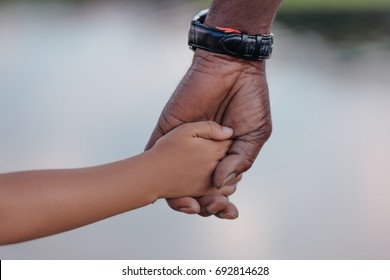 cropped view of african american grandfather holding hands with granddaughter