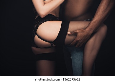 cropped view of african american man holding leg of sexy woman in lingerie isolated on black