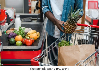 cropped view of african american man holding pineapple near supermarket counter