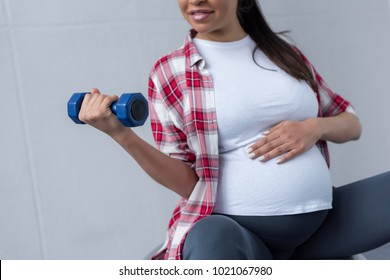 cropped view of african american pregnant woman exercising with dumbbell
