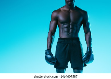 cropped view of african american sportsman in boxing gloves on blue background