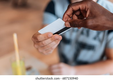 cropped view of african american waiter taking payment with credit card in cafe