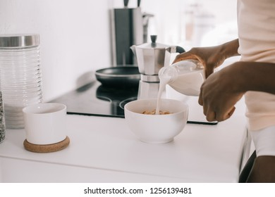 cropped view of african american woman pouring milk in bowl with cornflakes in kitchen