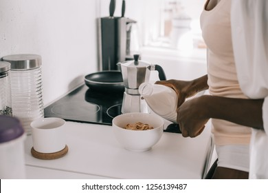 cropped view of african american woman pouring milk in bowl with cornflakes