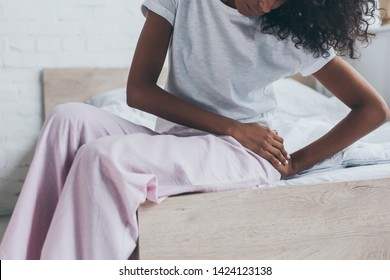 cropped view of african american woman suffering from pain in hip while sitting on bed