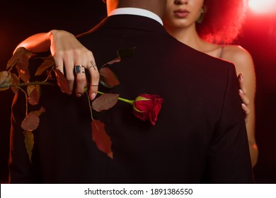 cropped view of african american woman holding rose and embracing man in formal wear on black