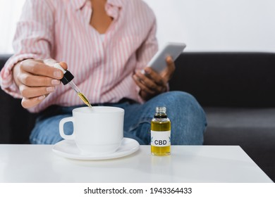 cropped view of african american woman holding smartphone and pipette with cbd liquid near cup of tea