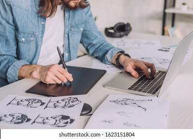 cropped view of animator using gadgets near sketches