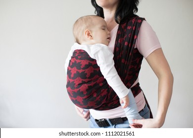 A cropped view of a baby in a woven wrap. A babywearing mother carrying her sleeping child in a sling.