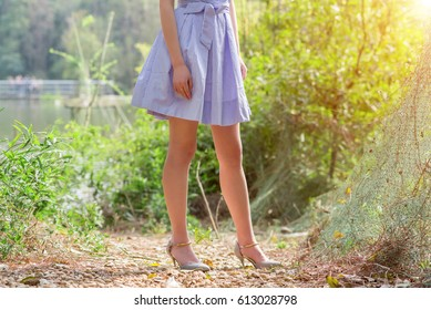 Cropped view of beautiful young woman walking in forest