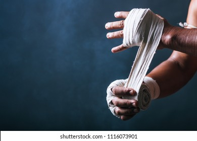 Cropped view of boxer wrapping his hands in dark gray backdrop.Copy space