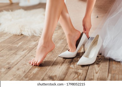 Cropped view of bride putting on wedding heels near dress at home