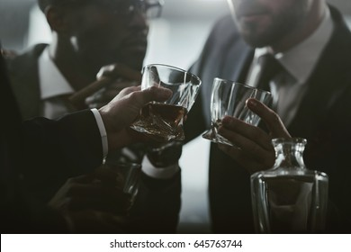 cropped view of business team spending time and drinking whiskey