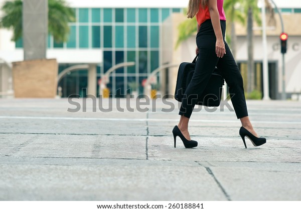 Cropped view of business woman walking in city street with laptop bag, commuting and going to work in the morning. Copy space, waist down