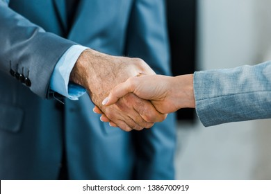 cropped view of businessman and businesswoman shaking hands