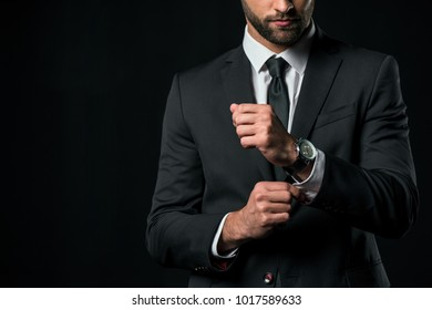 cropped view of businessman in jacket with wristwatch, isolated on black