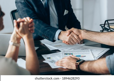Cropped view of businessman shaking hand with investor near colleague and papers on table