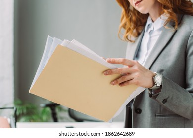 Cropped view of businesswoman leafing through paper sheets in folder with blurred workplace on background