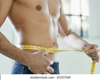 cropped view of caucasian young man measuring waist with yellow tape. Horizontal shape, mid section, side view