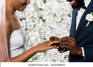cropped view of cheerful african american man putting wedding ring on finger of bride near flowers