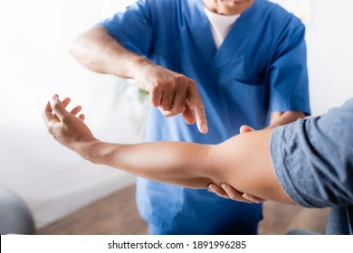 cropped view of chiropractor pointing with finger at injured arm of african american man in clinic