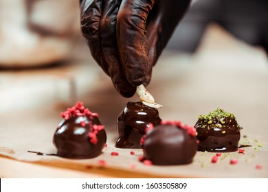 cropped view of chocolatier in black latex glove adding nuts on fresh made candies