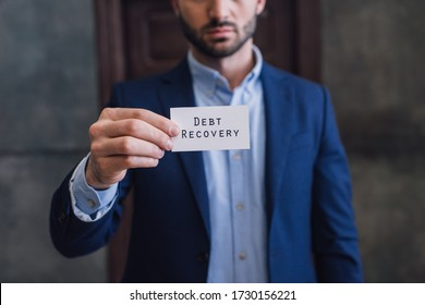 Cropped view of collector showing card with debt recovery lettering with outstretched hand