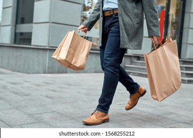 Cropped view of confident adult man in denim casual wear holding shopping paper bags in hands, walking at street on black friday