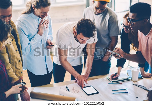 Cropped view of creative students solving training problems of planning while standing at desktop with sketches and blueprints in university interior.Hipster guys collaborating on new building project