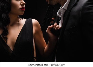 cropped view of dangerous woman holding gun near man in suit isolated on black